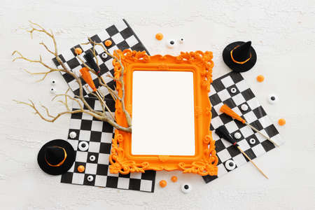 holidays image of Halloween. witcher hat, broom, trees, photo frame over white wooden table Standard-Bild