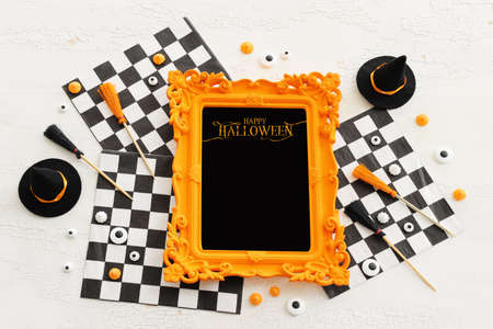 holidays image of Halloween. witcher hat, broom, photo frame over white wooden table