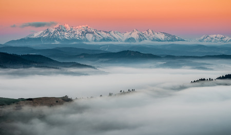 tatra: panorama over misty Spisz highland to snowy Tatra mountains in the morning, Poland landscape Stock Photo