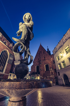 Mounument and st Barbaras church in Krakow, illuminated in the night, Poland