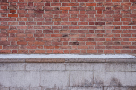 Vintage red brick wall with white limestone foundation