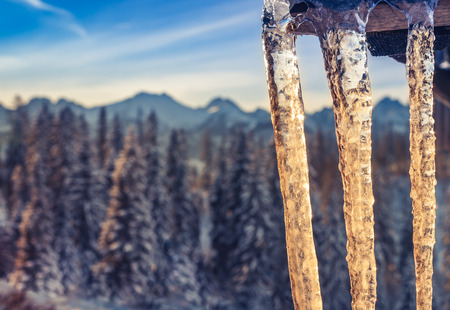 Icicles on wooden roof, Tatra mountains at winter morning