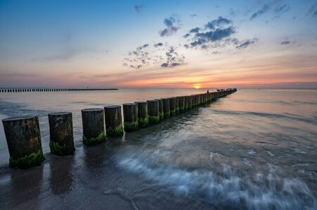 Baltic sea seascape at sunset, Poland, wooden breakwater and waves Stock fotó