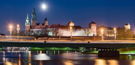 Krakow, Poland, Night panorama of Wawel Castle over Vistula river under full moon