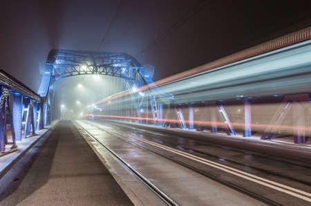 Krakow Poland, tram light trails on Pilsudski bridge over Vistula river in the night 스톡 콘텐츠