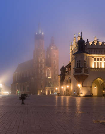 Main market square, Cloth Hall and St Mary's church in the misty night, Krakow, Poland