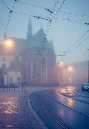 Picturesque old town Franciszkanska street and St Francis church on foggy morning, Krakow, Poland