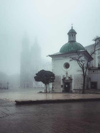 Main market square, St Mary's church and St Wojciech church in the autumn fog, Krakow, Poland