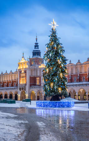 Cloth-hall (Sukiennice) in Krakow and Christmas tree on snowy winter morning, main square