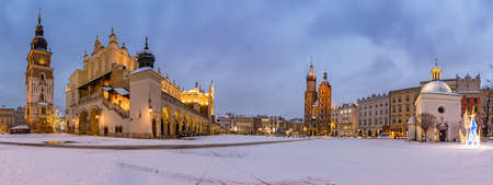Krakow, Poland, snowy winter Main Square night panoramic view with St Mary's church, Cloth Hall and Town Hall Tower 스톡 콘텐츠