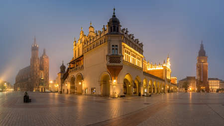 Krakow, Poland, main square night panorama with Cloth Hall and St Mary's church in the fog