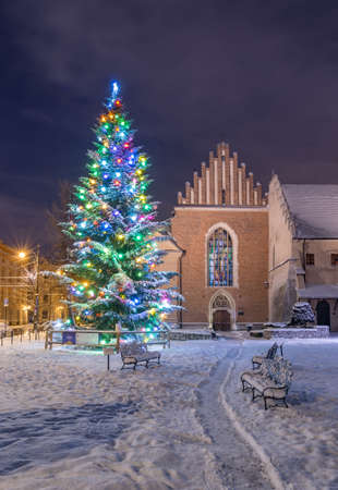 Winter in Krakow, Christmas Tree and St Francis church in the snow, night, Poland