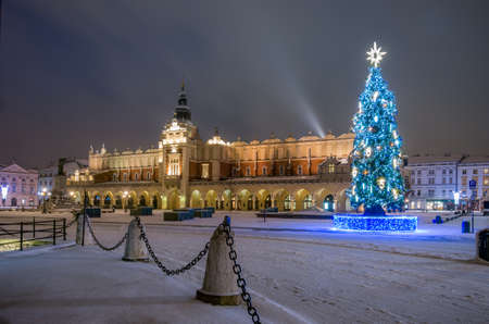 Cloth-hall (Sukiennice) in Krakow and Christmas tree on Main Square, snowy winter morning