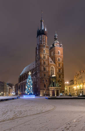St Mary's church on snow covered Main Square in winter Krakow, illuminated in the night