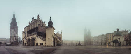 Krakow, Poland, main square panorama with Cloth Hall and St Mary's church on foggy November morning