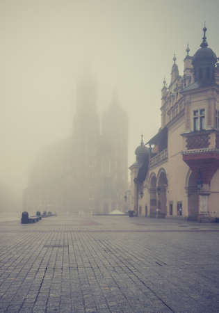 St Mary's church and Cloth Hall on Krakow Main Square in the thick fog, Poland.