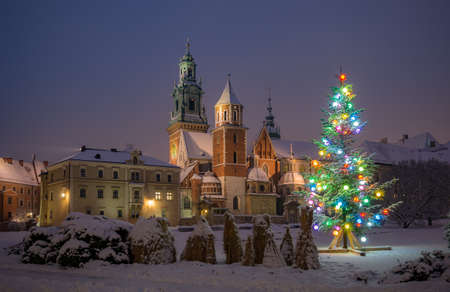 Illuminated Christmas tree on snow at night, Wawel cathedral and castle, Krakow, Poland 스톡 콘텐츠