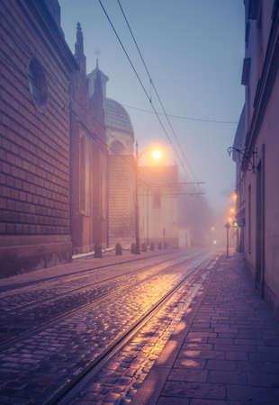 Picturesque old town Dominikanska street and Holy Trinity church on foggy night, Krakow, Poland 스톡 콘텐츠