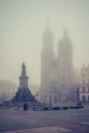 St Mary's church and Mickiewicz statue on Krakow Main Square in the thick fog, Poland.