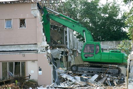 Medium weight shovel tearing down a building in preparation for construction. photo