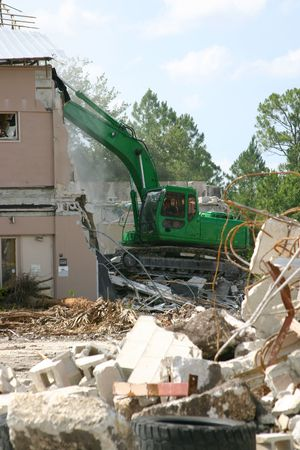 tearing down: Medium weight shovel tearing down a building in preparation for construction.