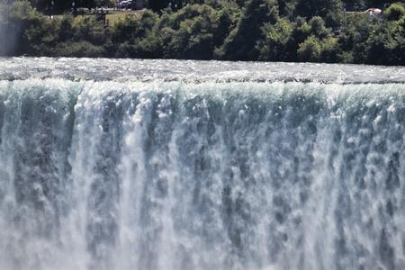 나이아가라 폭포 위에 쏟아지는 물 이미지는 호스 슈 폭포 위로 떨어지는 물을 보여줍니다.