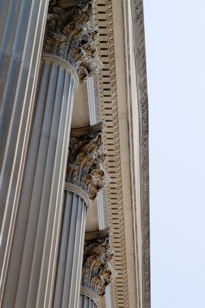 Stone columns of the National Archives Building, Washington, DC   in the Corinthian style  set against a blue sky