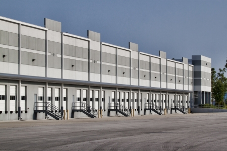 New warehouse space left empty by the economic downturn. Image shows the exterior of the building, including multiple closed and idle loading bay doors and a loading area devoid of any trucks.