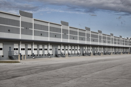 loading bay: New warehouse space left empty by the economic downturn. Image shows the exterior of the building, including multiple closed and idle loading bay doors and a loading area devoid of any trucks. Stock Photo