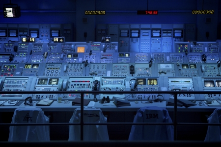 View of the restored Apollo 8 Launch Control room at Kennedy Space Center. The equipment has been moved to the Apollo  Saturn V Center. Image is lit with blue lighting and shows control panels, chairs and other equipment that was in use during the launch