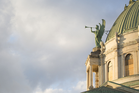 A copper-clad angel decorating the dome of a Roman Catholic Church trumpets the ending of a mid-Autumn day Stok Fotoğraf