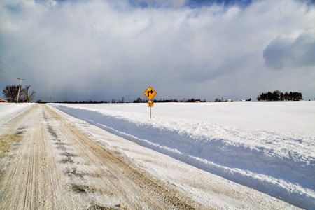 dormant: A lone traffic sign points the way from the edge of an empty, snow bound Western New York farm fields.