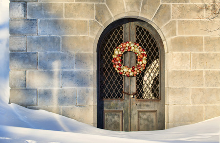 snows: Mausoleum with a Christmas wreath on the door sits silently in the deep snows of Winter in Buffalos Forest Lawn Cemetery.