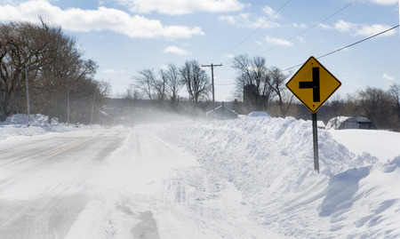 frigid: White-out conditions created by moderately strong winds blowing powder snow over the top of snow piles created by road plows. Stock Photo