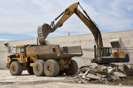 front end: A front end loader scoops rubble from a demolished building and loads it into a waiting dump truck. Stock Photo