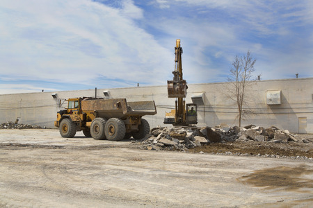 A front end loader scoops rubble from a demolished building and loads it into a waiting dump truck. Stock Photo