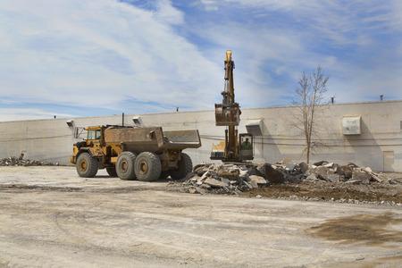 cargador frontal: Un cargador frontal cucharadas escombros de un edificio y lo carga demolido en un camión de volteo de espera.