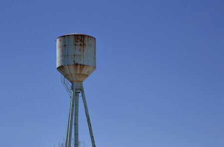rusting: An old rusting steel water tower shot against a clear blue sky. The tower is painted powder blue and shows signs of heavy rust.