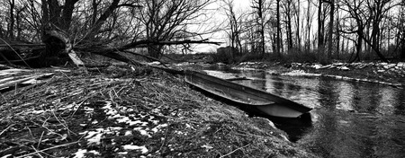 beached: A derelict flat-bottomed row boat is beached on the banks of Ellicott Creek in upstate New York. The remnants of sheets of ice from the once-frozen creek can be seen along the banks as well. is ice on