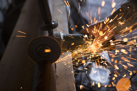 tradesman: Tradesman uses an electric grinder to cut a pipe in two. Image shows the tool, steel pipe, workmans hand and sparks from the cutting process.