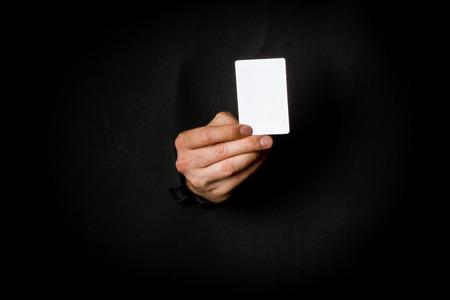 Hand through black paper