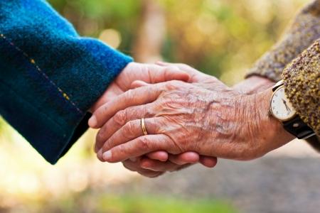 Bejaard paar holding hands buiten