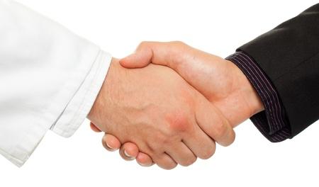 mani che si stringono: Stretta di mano tra un uomo d'affari e un medico, isolato su bianco.