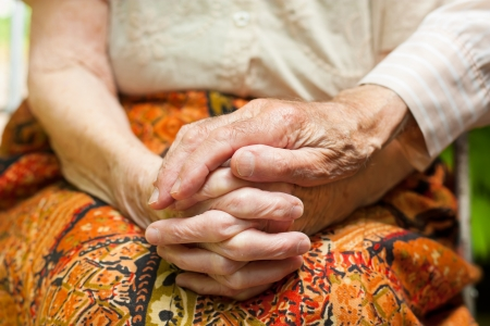 hard times: Elderly couple - the caring husband putting his hand on his wifes hands, showing love and support in hard times. Stock Photo