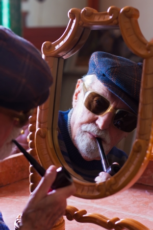 mirror image: Elderly man looking at himself in the mirror.