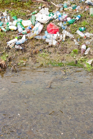 dumped: Plastic bottles and other garbage thrown on to the shore of a small river  Stock Photo