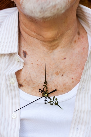 Clock hands placed on an elderly man photo