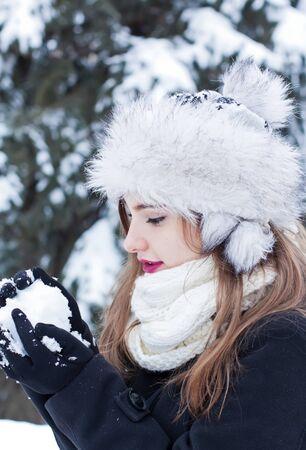 Beautiful young woman enjoying making a snowball. Imagens