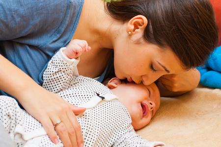 niño llorando: Joven madre calmar su llanto bebé con un beso. Foto de archivo