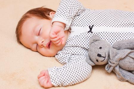 baby sleep: Little baby boy calmly sleeping with his teddybear. Stock Photo